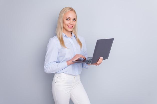 Foto del sorriso positivo del computer portatile della tenuta della ragazza del responsabile sulla parete grigia