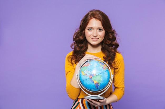 Foto della donna positiva della testarossa che porta i vestiti gialli che sorridono e che tengono il globo della terra sopra la porpora