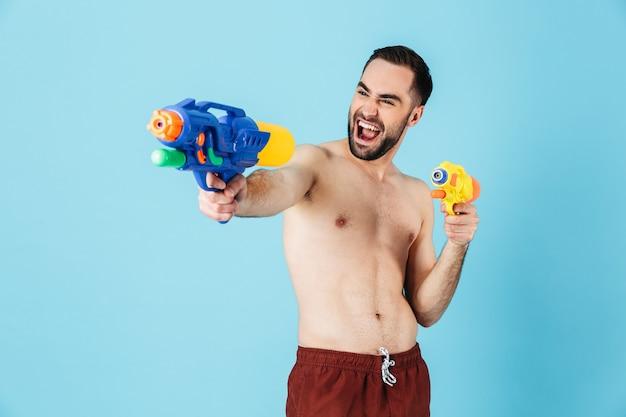 Foto di un turista positivo a torso nudo che indossa pantaloncini che ride mentre tiene in mano i giocattoli della pistola ad acqua isolati sopra il blu