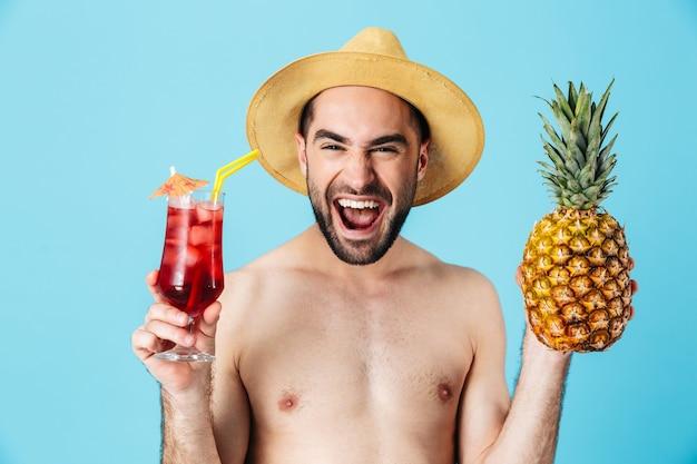 Foto di un turista positivo senza camicia che indossa un cappello di paglia che sorride mentre tiene in mano ananas e cocktail isolati
