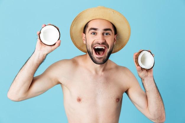 Foto di un turista positivo a torso nudo che indossa un cappello di paglia che sorride mentre tiene in mano due parti di cocco isolate sopra il blu