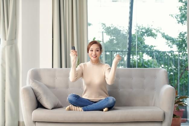 La foto di una giovane donna sorpresa positiva sul divano al chiuso a casa guarda la tv fa il gesto del vincitore.