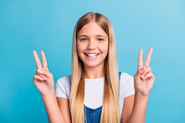 Foto di una ragazza bionda positiva che mostra il v-sign nella telecamera indossa una maglietta bianca isolata su uno sfondo di colore blu pastello