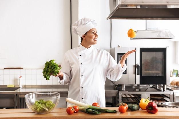 Foto di chef donna positiva che indossa un pasto di cucina bianco uniforme con verdure fresche, in cucina al ristorante