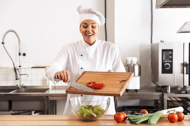 Foto di chef donna positiva indossando l'uniforme bianca che produce insalata con verdure fresche, in cucina al ristorante
