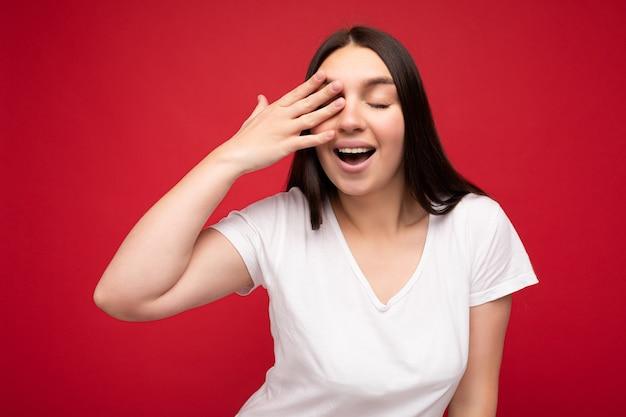 Foto di positivo giovane bella persona di sesso femminile bruna con emozioni sincere che indossa t-shirt bianca casual per mockup isolato su sfondo rosso con copia spazio e occhio di copertura.