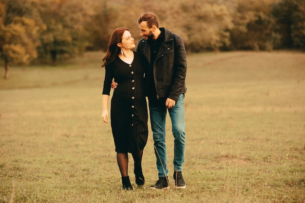 Foto di coppia incinta, camminando nel parco e guardando l'altro