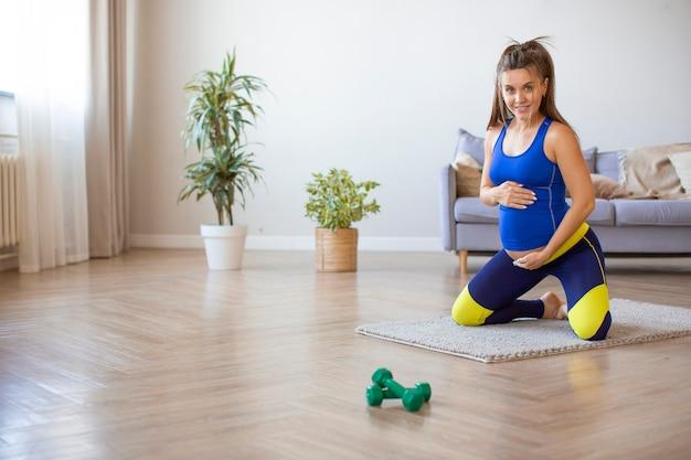 Foto di una donna incinta che fa yoga nell'interno domestico