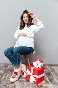 Foto di una donna incinta con regali a figura intera che guarda l'obbiettivo