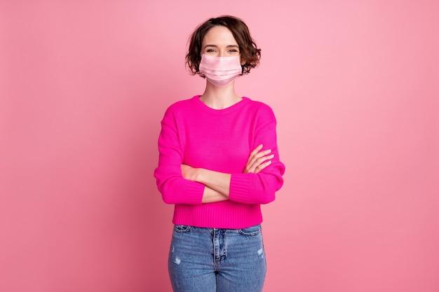 Foto di una bella signora allegra attraente persona sicura di sé braccia incrociate buon umore indossare maglione casual pullover maschera medica jeans isolato rosa pastello colore sfondo