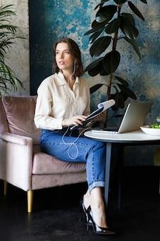 Foto di abbastanza bella giovane donna seduta in un caffè al chiuso utilizzando laptop tenendo i documenti che parlano dal telefono cellulare.