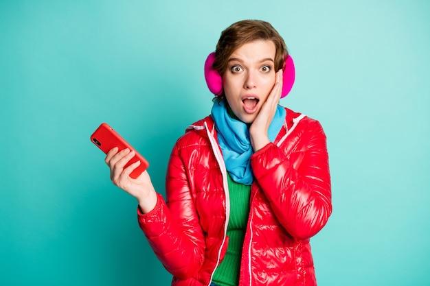 Foto di bella signora matta bocca aperta tenere il telefono mano sullo zigomo bot credere che molti seguaci indossano sciarpa cappotto rosso copri orecchie rosa ponticello verde isolato parete color verde acqua