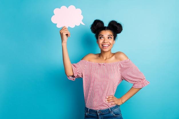 Foto di bella pelle scura lady tenere vuoto nuvola di carta guardare sognante pensare al discorso creativo indossare strisce bianche rosse off-spalle camicetta jeans isolato blu parete di colore