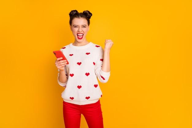 La foto della signora piuttosto eccitata tenere le mani del telefono alza il pugno dell'umore estatico ha un pullover bianco con motivo a cuori di usura di investimento iniziale