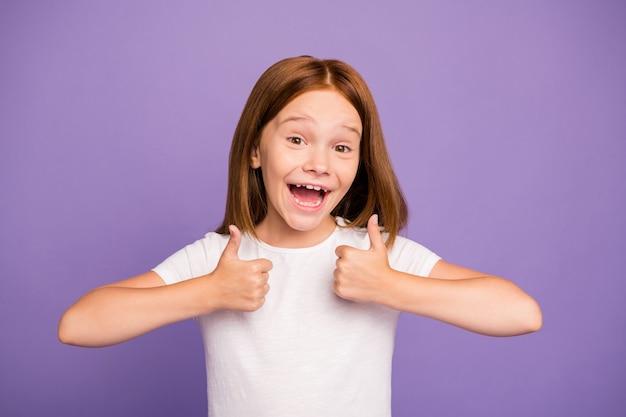Foto della piccola ragazza abbastanza eccitata dello zenzero che solleva i pollici in su