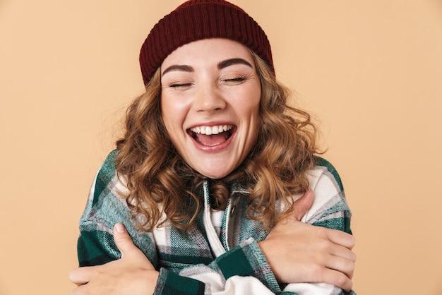 Foto di una donna piuttosto eccitata con un cappello a maglia che si abbraccia e ride isolata sul beige