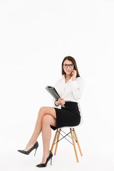 Foto di una bella donna d'affari lavoratrice vestita in abiti formali che parla allo smartphone mentre è seduta su una sedia da ufficio isolata su un muro bianco