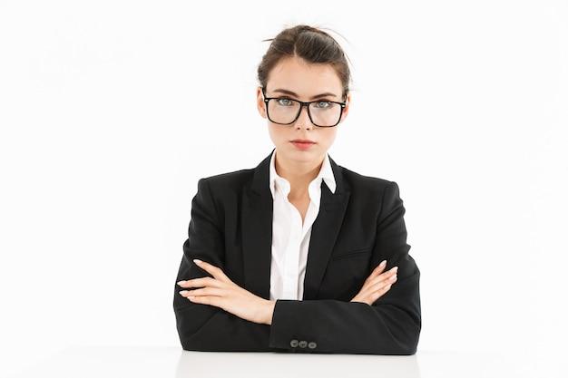 Foto di una bella donna d'affari lavoratrice vestita con abiti formali mentre lavora e si siede alla scrivania in ufficio isolata su un muro bianco