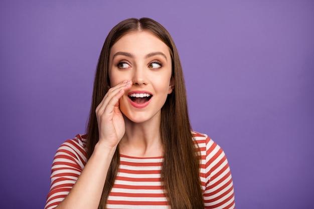 Foto di piuttosto divertente curioso signora guardare lato spazio vuoto mano vicino alla bocca dire dire notizie pettegolezzi persone folla indossare casual camicia a righe isolato pastello viola parete di colore