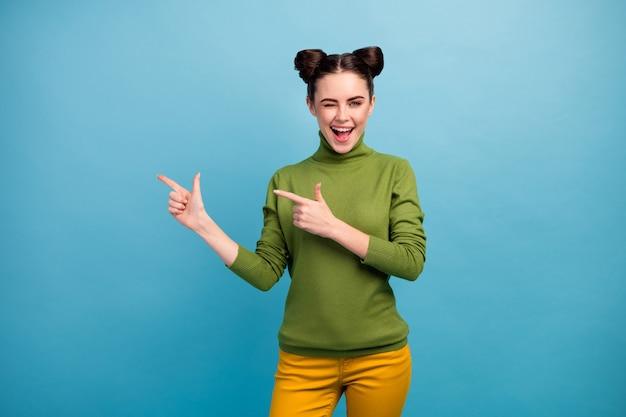 Foto di bella signora divertente lato dito diretto spazio vuoto offrire prezzi bassi shopping flirty occhiolino indossare dolcevita verde pantaloni gialli isolato blu parete colore