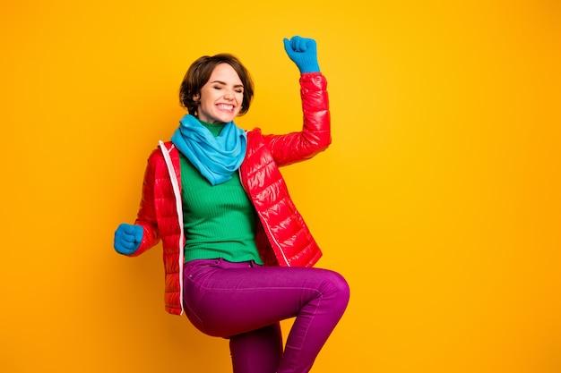 Foto di una signora abbastanza divertente dall'umore estatico che si rallegra che celebra il successo indossare soprabito rosso casual guanti sciarpa blu pantaloni a collo alto verde