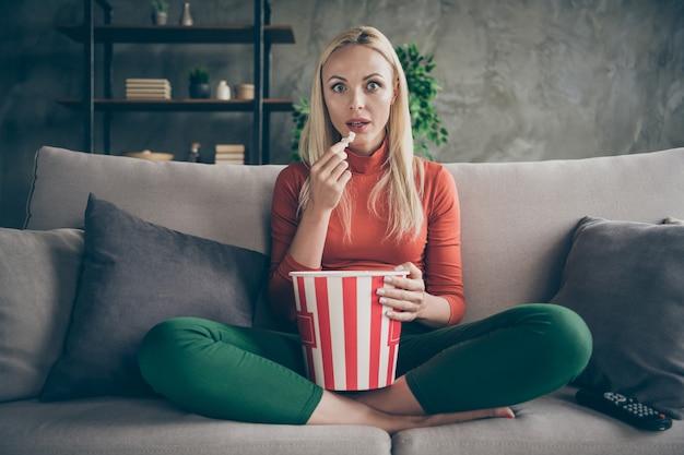 Foto di umore casalingo abbastanza divertente della signora che mangia popcorn guardando la televisione spettacolo horror occhi pieni di paura seduta comfort divano vestito casual appartamento soggiorno al chiuso