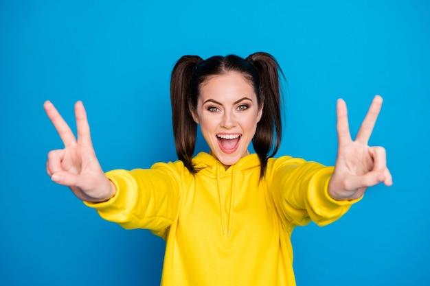Foto di una signora piuttosto divertente con due code pettinatura alzare entrambe le braccia mostrando il simbolo del segno v buon umore allegro dire ciao amici indossare casual felpa con cappuccio gialla pullover isolato sfondo di colore blu brillante
