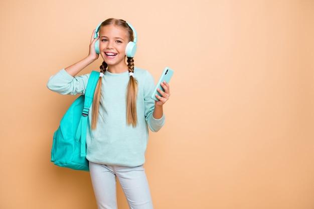 Foto di piuttosto divertente piccola signora ascolta auricolari gioventù canzone moderna a piedi scuola navigazione telefono indossare borsa teal pullover blu jeans isolato beige pastello parete di colore