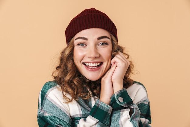 Foto di una donna abbastanza felice con un cappello lavorato a maglia in posa e sorridente isolato su beige