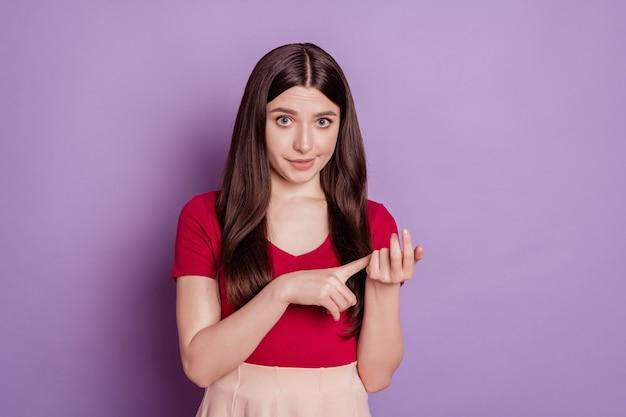 Foto di una ragazza piuttosto irritata che contano le dita e guarda la telecamera infastidita dal viso su sfondo viola