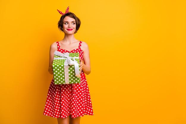 Foto di bella signora tenere grande scatola regalo verde guardare lato spazio vuoto ingannevole eccitato compleanno ragazza indossare stile retrò estate punteggiata rosso bianco vestito fascia isolato muro di colore giallo