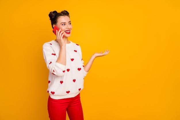 La foto della bella signora tiene la mano del telefono che parla al migliore amico che racconta la storia di un appuntamento romantico ispirato al pullover bianco con motivo a cuori