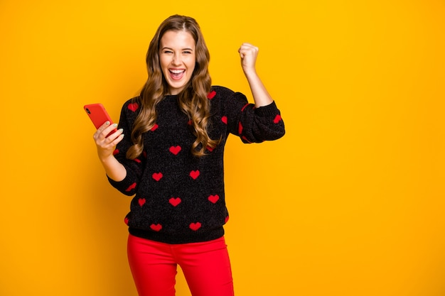 Foto di bella signora tenere le mani del telefono leggere fidanzato romanticismo data invito celebrare il successo alzare pugno indossare pantaloni modello pullover cuori