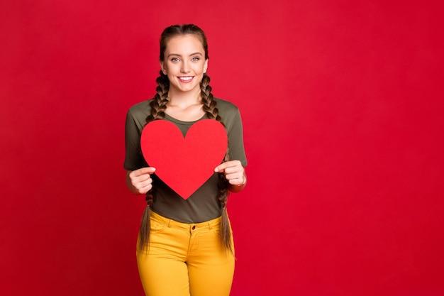 La foto della signora graziosa che tiene il grande cuore di carta che mostra la cartolina dell'invito di promenade stupefacente indossa la maglietta gialla casuale di colore rosso isolato della maglietta verde dei pantaloni