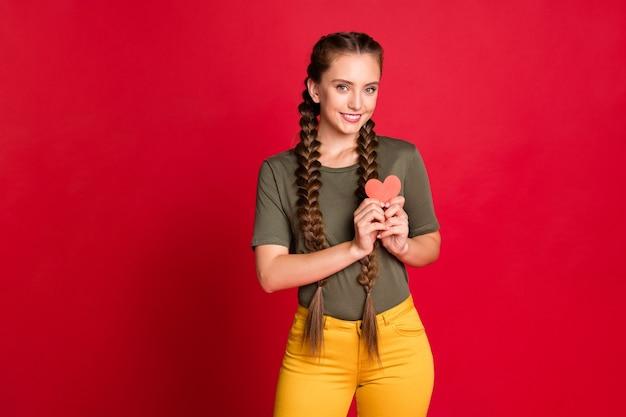 Foto di bella signora che tiene piccola cartolina cuore di carta vicino al seno che esprime cardiologia concetto di sicurezza indossare pantaloni gialli casual t-shirt verde isolato sfondo colore rosso