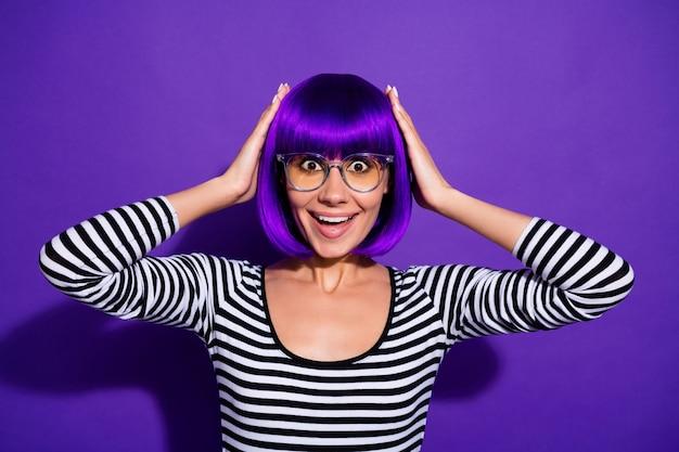 La foto della signora graziosa ascolta il fondo porpora isolato del pullover a strisce della parrucca di spec