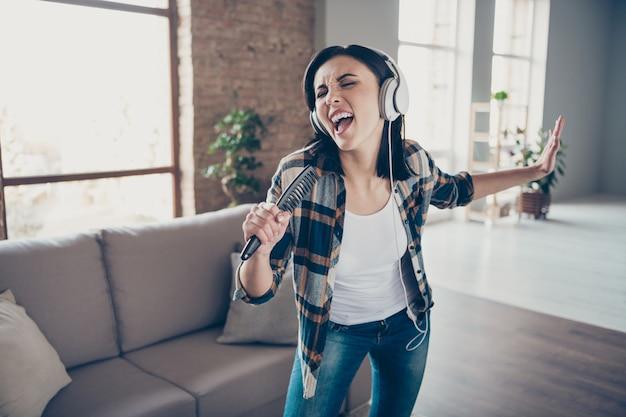 Foto di bella signora che si rallegra ascoltando la melodia preferita nei moderni paraorecchie ballando e cantando nella spazzola per capelli preparazione concerto indossare abiti casual appartamento al chiuso