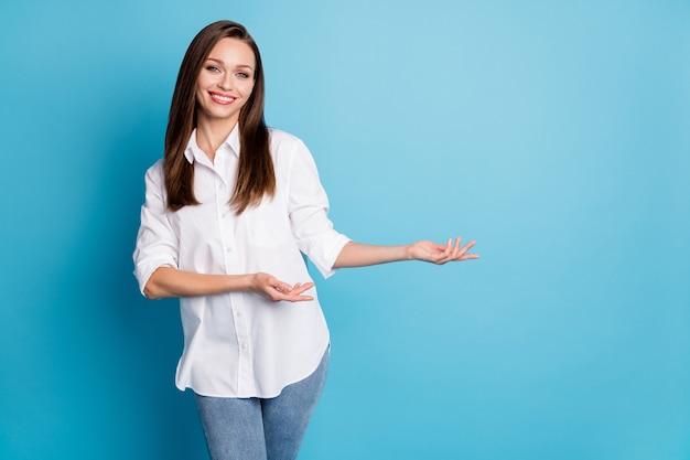 Foto di una graziosa signora manager che mostra le braccia spazio vuoto novità indossa jeans camicia bianca isolato sfondo blu colore