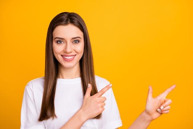 Foto di bella signora di affari che dirige le dita indice lato spazio vuoto fresco incredibile offerta indossare maglietta bianca casual isolato muro di colore giallo vivido