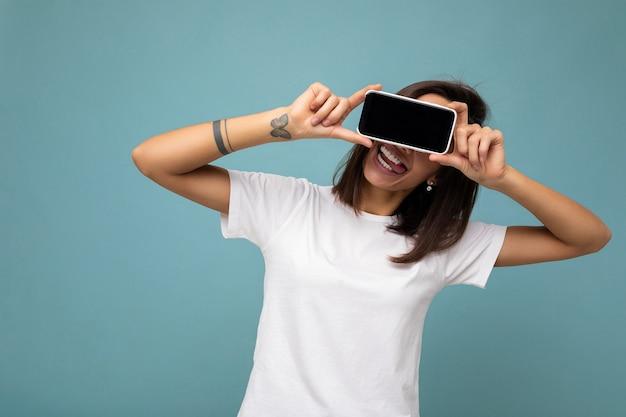 Foto di una donna bruna adulta piuttosto positiva di bell'aspetto che indossa una maglietta bianca in piedi isolata su