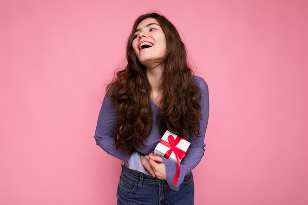 Foto di giovane donna riccia bruna sorridente abbastanza positiva isolata su sfondo rosa