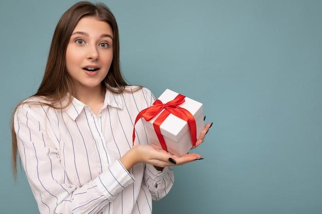 Foto di giovane donna castana sorpresa abbastanza positiva isolata sopra la parete blu del fondo che porta la camicia bianca che tiene il contenitore di regalo bianco con il nastro rosso e che guarda l'obbiettivo. copia spazio, mockup