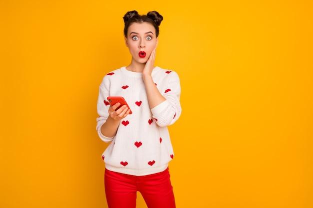 La foto del telefono della stretta della signora piuttosto scioccata ha letto la mano di una brutta notizia terribile incredibile sulla guancia che indossa un pullover bianco con motivo a cuori