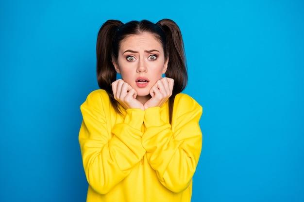 Foto di una signora piuttosto terrorizzata a due code pettinatura bocca aperta guarda notizie quarantena continua braccia sugli zigomi indossare casual felpa gialla pullover isolato blu brillante sfondo di colore