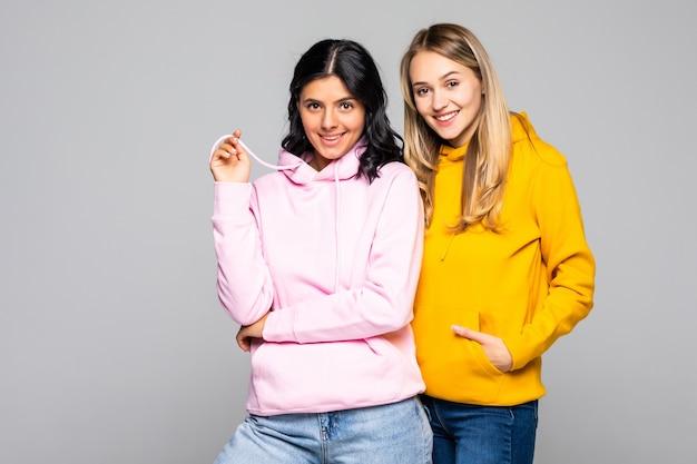 Foto di due belle donne che indossano felpe casual e jeans isolati muro bianco