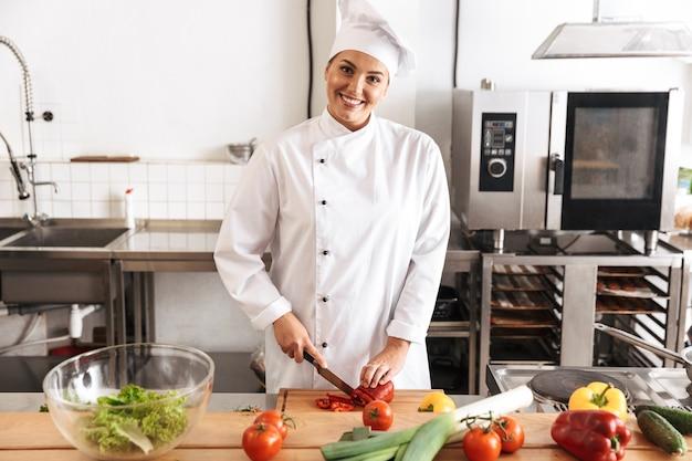Foto di chef donna graziosa che indossa l'uniforme bianca che produce insalata con verdure fresche, in cucina al ristorante