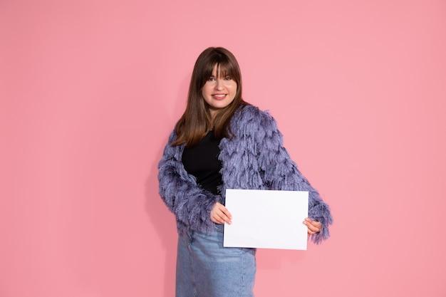 Foto di abbastanza giovane donna dai capelli scuri. contiene un foglio di carta bianco, pulito e bianco per i sorrisi di iscrizione, guarda nella cornice. foto su sfondo rosa in studio.