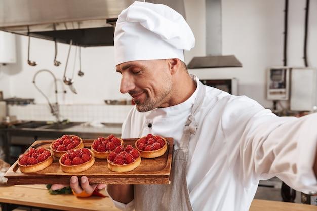 Foto del capo maschio professionista in uniforme bianca prendendo selfie e tenendo il piatto con torte