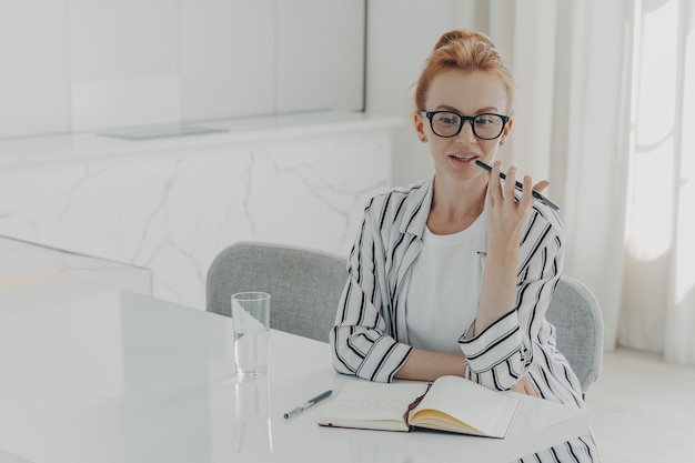 La foto di una giovane donna dai capelli rossi registra una chiamata vocale tramite il microfono dello smartphone seduta sul desktop
