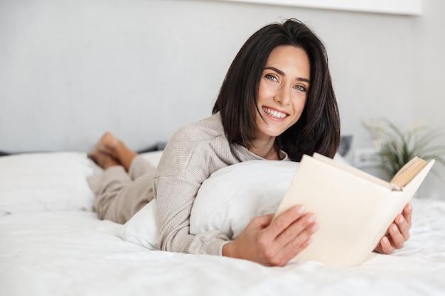 Foto di una donna rilassata degli anni '30 che legge un libro, mentre giaceva a letto con lenzuola bianche a casa